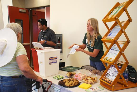 """Waste Management's Julianne Fulton discusses proper disposal of sharps and pharmaceuticals with a resident at the """"Round Up."""""""
