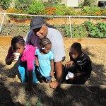 Wyatt Coleman and grandchildren admire their plot of vegetables at Planting the Seeds of Life.