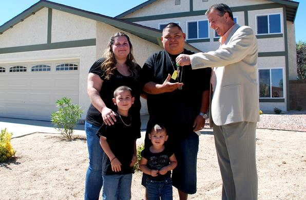 Palmdale Mayor Jim Ledford presents house keys to Salvador and Natasha Almanza who purchased the first of the City's rehabbed homes through the Homeownership Assistance Program.