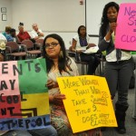 Students hold up signs in protest of the Antelope Valley College pool closure during Monday evening's Board of Trustees meeting.
