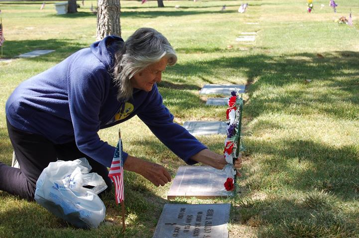 Lancaster resident Sharon Parizo came took time out from the ceremony to place flowers at the gravesite of her father, Earl A. Parizo, a World War II veteran who passed away in 1993.