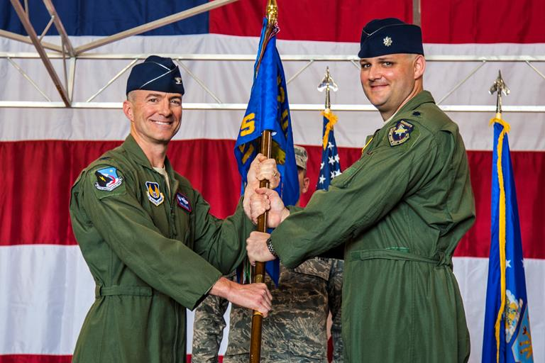 Col. Christopher Azzano, former 412th Operations Group commander, hands the 461st Flight Test Squadron guidon to Lt. Col. Andrew Allen during a change of command ceremony June 11. Allen assumed command of the squadron, which conducts developmental testing for the F-35 Joint Strike Fighter. (Courtesy photo by Darin Russell/Lockheed Martin)