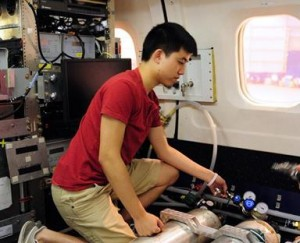 SARP participant Braven Leung assists in testing the University of Houston air quality instruments onboard the DC-8.
