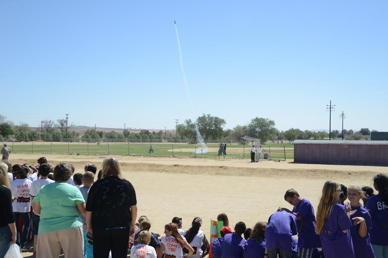 "Onlookers watch a rocket soar into the ""stratosphere"" during the 1st Annual Edwards Intermediate Space Challenge held at Branch Elementary. (U.S. Air Force photos by Kenji Thuloweit)"