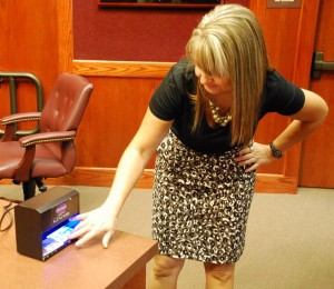 Kery German demonstrates the use of a counterfeit detector.