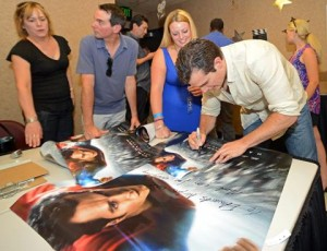 "Cavill signs ""Man of Steel"" posters in a VIP room before the start of the movie."