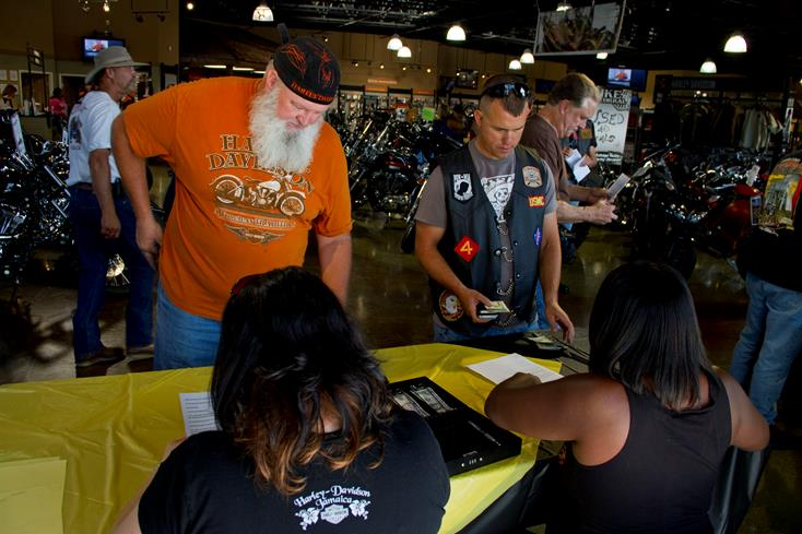"""A line begins to form as people buy shirts and raffle tickets to support """"The Fallen."""""""