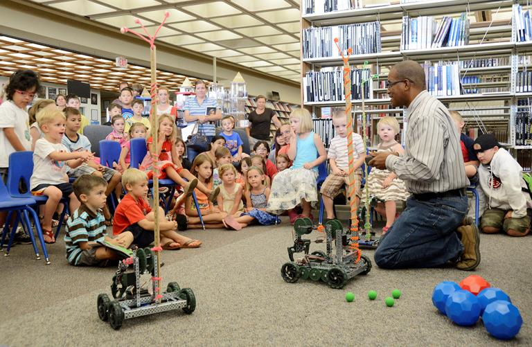 412th Test Wing Science, Technology, Engineering and Mathematics outreach director, Mickey Bowen, uses VEX Claw bots to teach children about motors during the base library's summer reading program. (U.S. Air Force photo by Rebecca Amber)