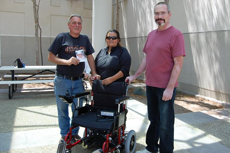Andy and Angie Smith (left) donated their late mother's barely to Bill Martin (not shown) whose wheelchair was stolen on the 4th of July. Martin's caretake, Robert Hukill (right), accepted the donation Thursday (July 18).