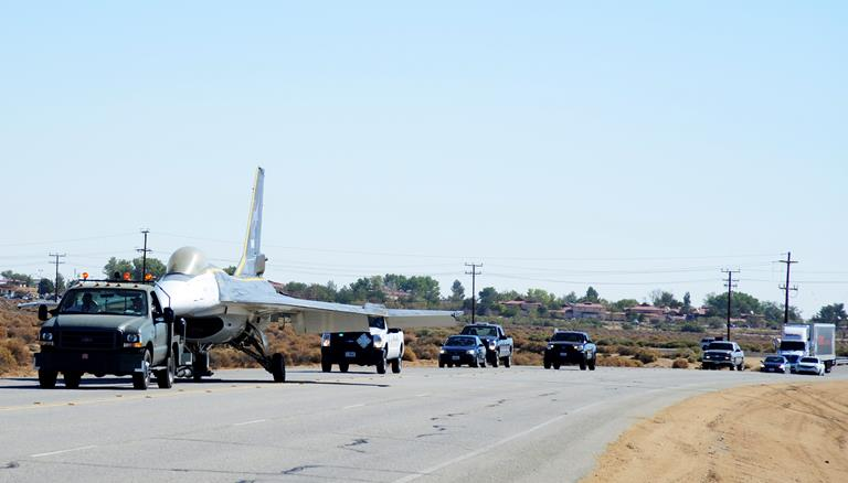 Traffic was stopped as the F-16XL was transported west down Rosamond Blvd. towards its new home at the Air Force Flight Test Museum on Aug. 9, 2013. The F-16XL, an experimental fighter, is a derivative of the F-16 that was used to explore the advanced cranked-arrow delta wing. The plane was one of three aircraft transported to the AFFT Museum from their restoration home in Hangar 1864. (U.S. Air Force photo by Rebecca Amber)