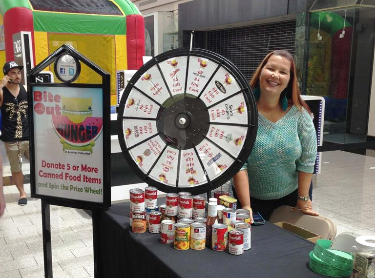 Guests that donated 5 or more canned food items got to spin the prize wheel and win $5-$10 gift cards to restaurants and eateries in the mall.   Pictured: AV Mall Marketing Director Tricia Granger