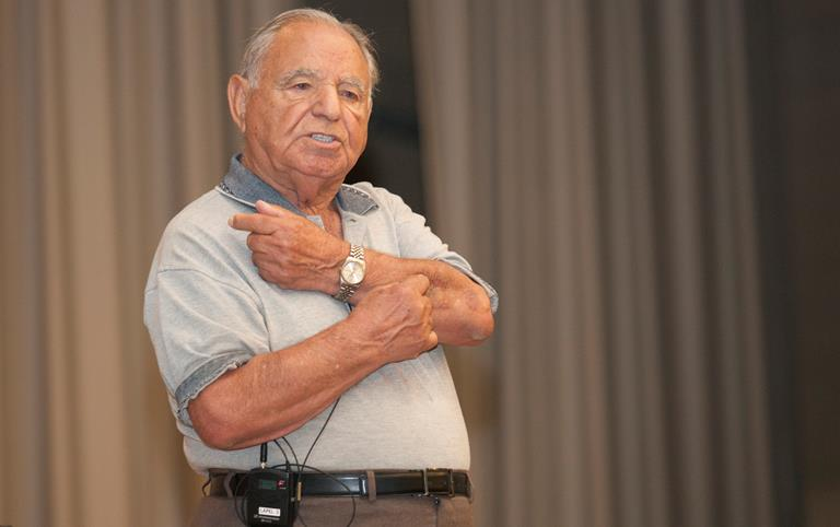 Holocaust survivor Albert Rosa talks about his life during the Nazi Germany occupation of his native Greece and being transported to a concentration camp in Poland later on. (U.S. Air Force photo by Jennifer R. Correa)