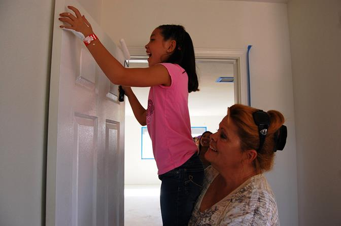 "Eight-year-old Chayse gets a helping hand from Acton resident Tami Lamb in painting a door in one of the bedrooms that will be converted into a music room. ""I heard about [the cleanup] on Facebook so I decided to come,"" Lamb said. ""Kids need a place to go and this is important."""