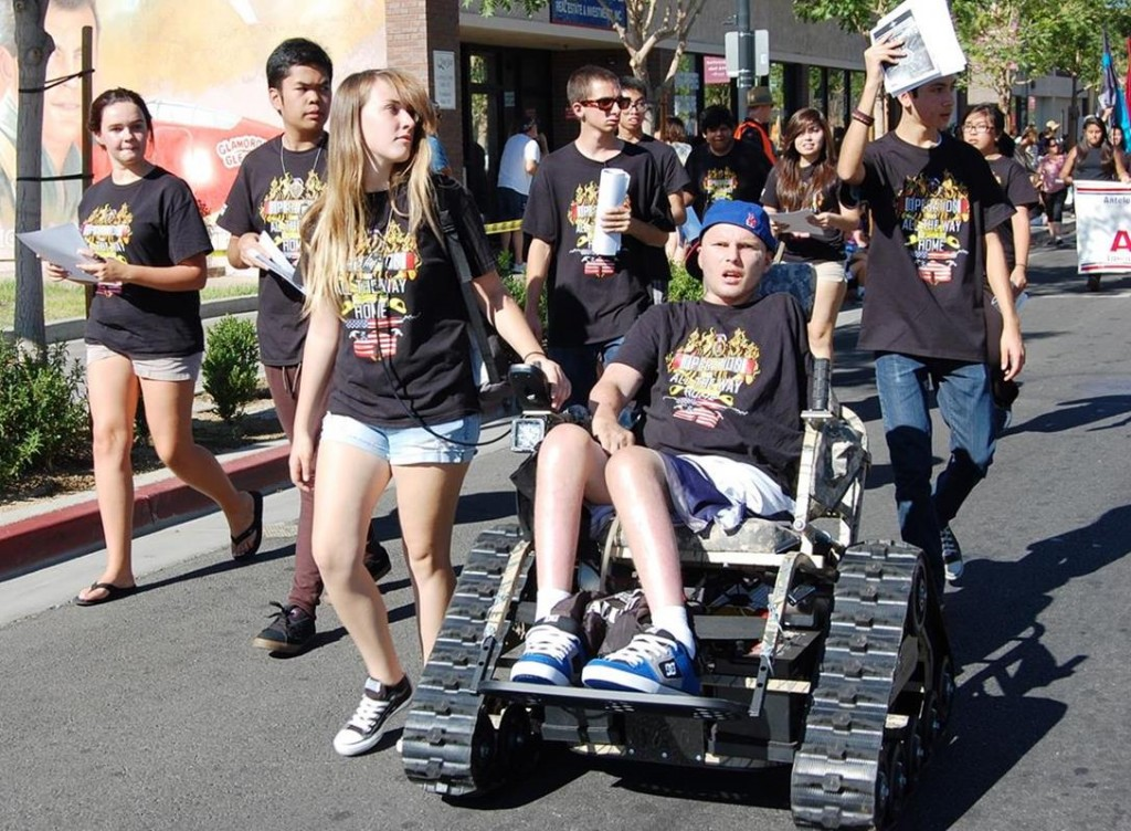 "Lancaster High School students brought ""Operation All the Way Home"" to the AV Fair Parade on Aug. 17. The students will receive the first ""Veteran's Community Service Award"" for their commitment to raising the funds necessary to purchase a family home for disabled Antelope Valley veteran Jerral Hancock (sitting)."