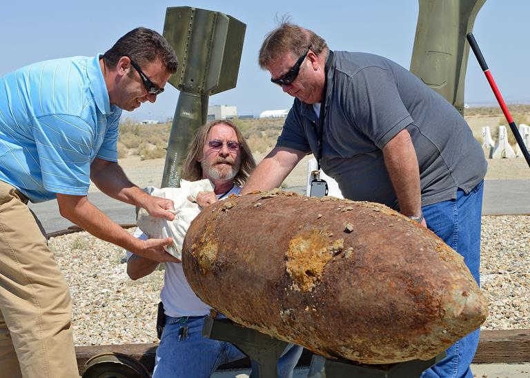 (From left to right) William Jones, Jon Wiggins and James McCaffrey remove items from a time capsule last week in front of the 412th Maintenance Squadron Munitions Flight storage area. The time capsule was assembled and buried on Feb. 24, 1993, by all three while they were on active duty status with the then 6515th Munitions Maintenance Squadron. (U.S. Air Force photo by Jet Fabara)