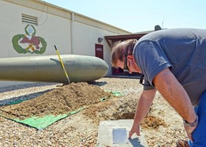 James McCaffrey, 412th MXS time changer manager, reads the plaque of the time capsule. (U.S. Air Force photo by Jet Fabara)