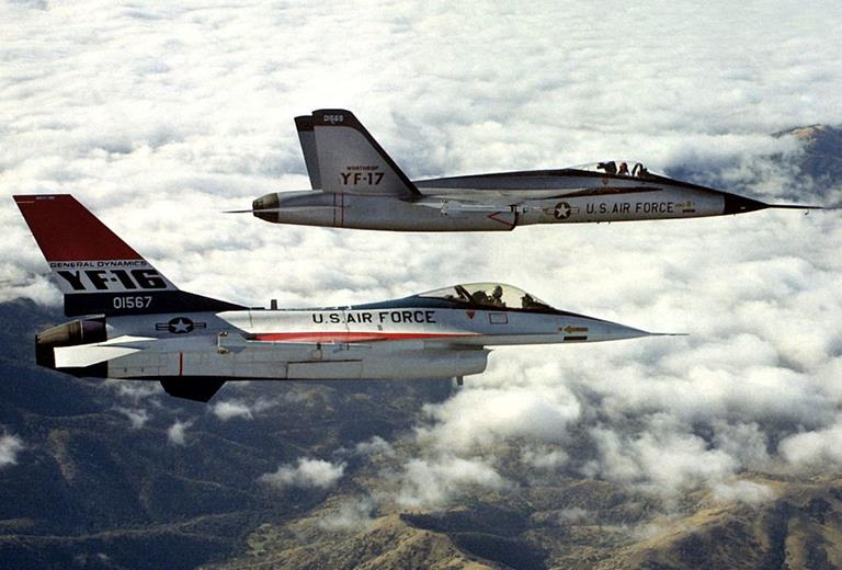 An air-to-air right side view of a YF-16 aircraft and a YF-17 aircraft, side-by-side, armed with AIM-9 Sidewinder missiles. (Photo courtesy United States Air Force.)