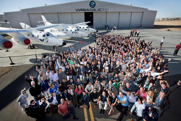 A majority of Virgin Galactic's future Astronauts gather with Sir Richard Branson (center) for a group photo at Virgin Galactic FAITH hangar in Mojave on Wdnesday. At the side is the WhiteKnight2 mated with SpaceShip2. (Photo by MARK GREENBERG)
