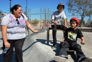Proud mom, Melanie Rhoda, takes a break with son, Robert, and skateboarder, Nick Livigni.
