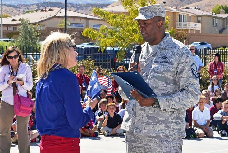 Master Sergeant Bonner presents a flag that flew over the US Base in Guantanamo Bay to Gregg Anderson Academy Principal Shelly Dearinger. (Courtesy TOM LLEWELLYN)