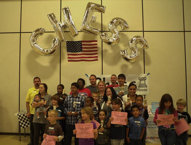 """Tournament winners gather in front of the AV Chess House banner for a group photo after the first annual """"Chess Makes a Difference"""" Day Chess Spectacular's Awards Ceremony."""