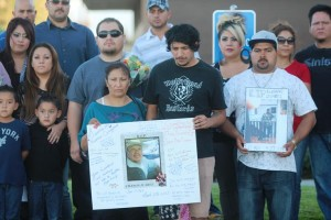 The victim's wife, Maria, and son, Victor, hold a poster of Luciano Meza Juarez at a candlelight vigil on Oct. 1, 2013. (Photo by TONY CHEVAL)