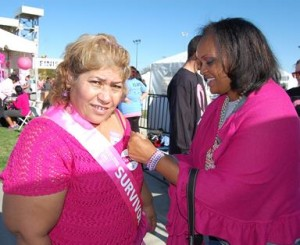 Supporter Waunette Cullors (right) pins 25-year breast cancer survivor Elena Vasquez.