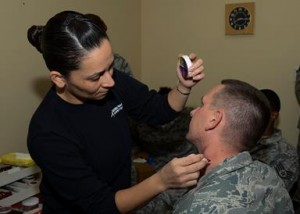 Master Sgt. Justin Jerome (right) volunteered to have scratch marks created on his neck to show that men are victims of domestic violence too. (Rebecca Amber)