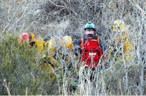Emergency responders work to get the body from the bottom of the ravine. (JOHN MEZA)