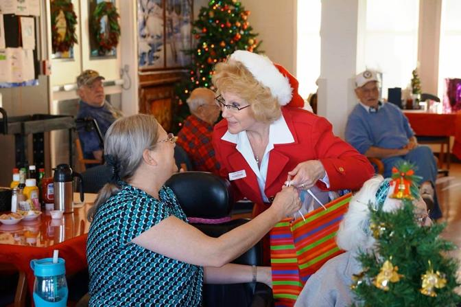 GAVAR's Mrs. Claus (CEO Pamela Vose) presents a resident veteran with a gift at the Pete Knight Veteran's Home in Lancaster.