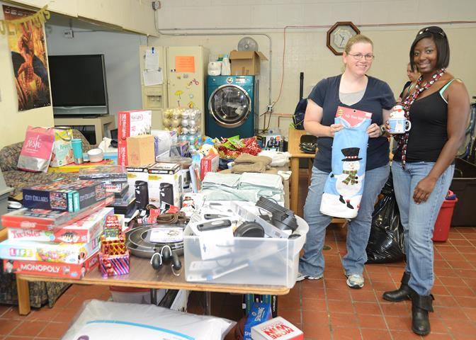 Calla Hines (left) and Japhia Logan, Airman's Attic lead volunteers, show off items donated by the Lancaster Rotary Club Dec. 3. The club purchased $1,600 worth of items to help out young Airmen who can come to the Airman's Attic and pick up items free of charge. (U.S. Air Force photo by Kenji Thuloweit)