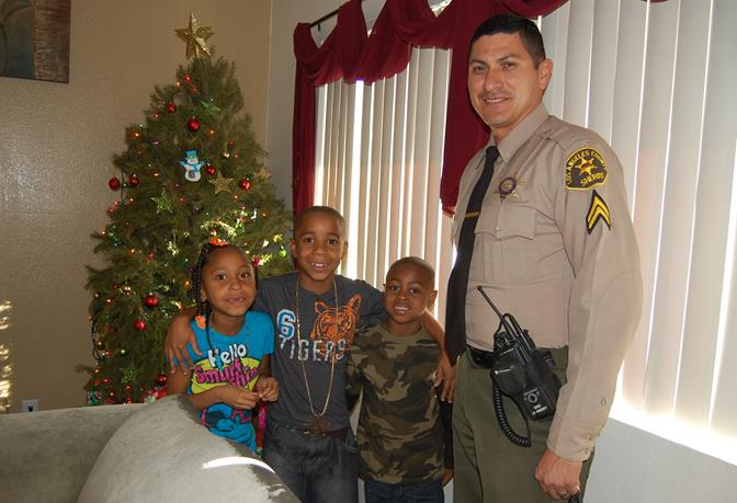(L to R) Amira Jackson, Amari Black, Devonte Smith and deputy Miguel Ruiz. Ruiz hand-delivered presents to the children Tuesday. The gifts came from the Lancaster Sheriff Station's annual Holiday Food and Toy Drive.