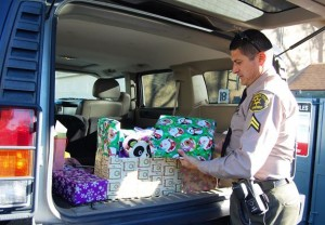 Ruiz checks his stack of presents before heading to Lake Los Angeles to hand deliver gifts to another family.