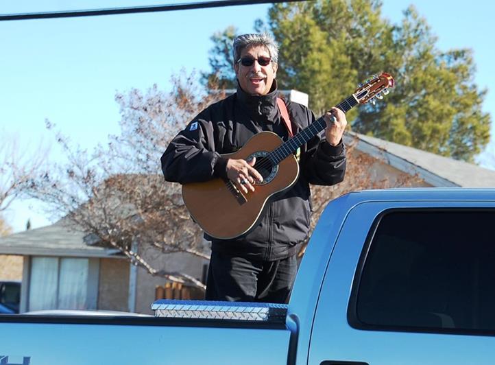 "Isaac Barcelona strummed his guitar while serenading the crowd with ""Feliz Navidad."""