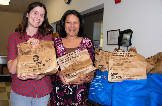 SAVES Coordinator Patricia Morales (right) and SAVES employee Katherine Stocking pose for a picture with two of the nearly 300 holiday family dinner packages that were distributed to local, disadvantaged families on Monday (Dec. 23).