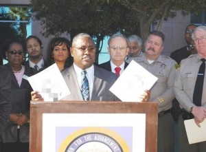 NAACP President V. Jesse Smith holds up two versions of the hate fliers. <em>(Content blocked by Editor. Click image to view unedited version)</em>