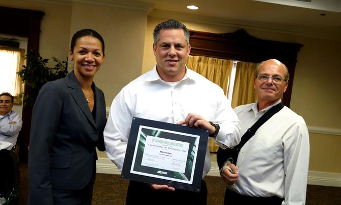 Pamela Manning (left) and Tony Antich (right) present a certificate of  participation to Palmdale's Mike Behen.