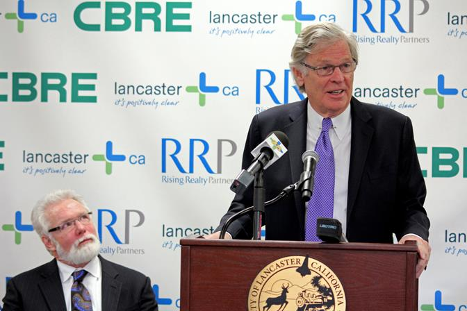 Rising Realty Partners CEO Nelson Rising speaks at a press conference to announce the acquisition as Lancaster Mayor R. Rex Parris looks on.
