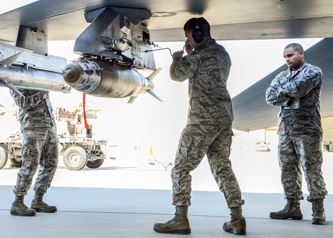 Airman 1st Class Maurice Appleton (center) is evaluated as he loads the GBU-38 JDAM onto an F-16 while Staff Sgt. Dustin Jones (left) works on the AIM-120 AMRAAM. (U.S. Air Force photo by Rebecca Amber)