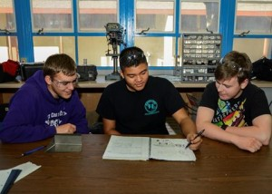 (left to right) Co-captain, Larson LeDuc, Team member, Anthony Quinnert and Team captain, Geoffrey Holmes, grade 12, study their engineering notebook. (Rebecca Amber)
