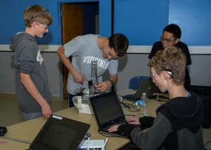 Members of the team work on fine-tuning an arm to be integrated in their robot Scoop Da Whoop. (Rebecca Amber)