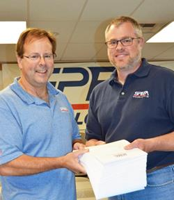 """SPEEA's Rich Plunkett, left, and Matt Kempf hold more than 400 of the """"make whole"""" awards Boeing was ordered to pay employees by an arbitrator's ruling. Each sheet represents an award of at least $100,000."""
