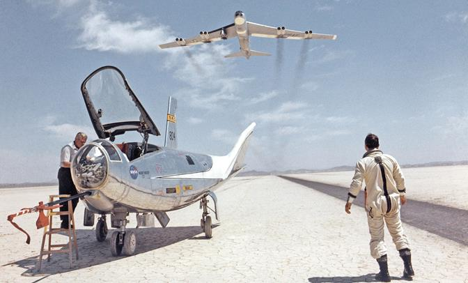 In this classic photo from Nov. 30, 1968, NASA research pilot Bill Dana takes a moment to watch NASA's NB-52B mothership launch aircraft cruise overhead after Dana piloted the HL-10 lifting body to a landing on the bed of Rogers Dry Lake at Edwards Air Force Base, Calif., after a research flight. (NASA photo)