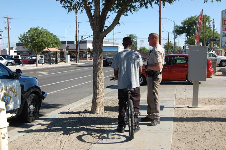 """CHP Officer K.D. Wheeler stopped a bicyclist for riding on a sidewalk on 50th Street West near Columbia Way. The rider was given a warning and a bicycle safety brochure. """"He needs to be riding in the bicycle lane,"""" Hernandez said."""