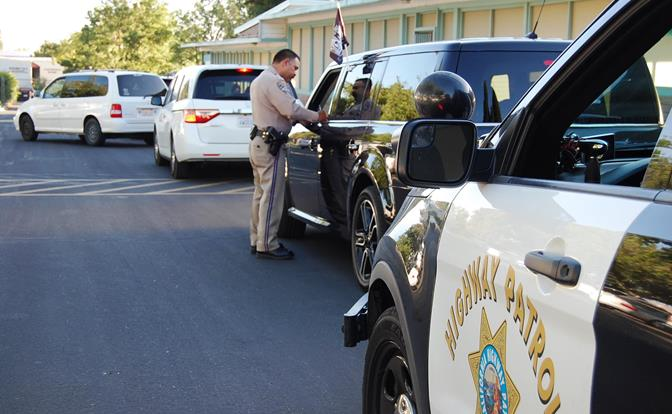 """CHP officer Gil Hernandez cites a driver in front of Quartz Hill Elementary for having a 6-year-old in the front passenger seat. """"[The child] needs to be in a booster seat or the proper child restraint system for him to be safe,"""" Hernandez said."""