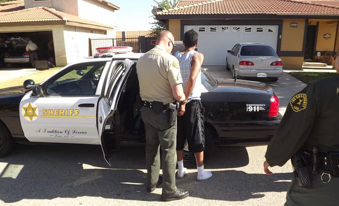 A suspect is taken into custody Tuesday during a massive search warrant operation, which focused on juveniles responsible for an east Palmdale crime spree. (Photo courtesy LASD)