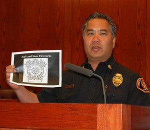 Los Angeles County Fire Department Battalion Chief Wes Anzai holds up an image of the official label of the State Fire Marshal. All Safe and Sane fireworks bear the official seal, Anzai said.