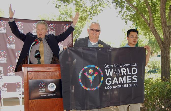 """(L to R) Bill Shumard , President/CEO of Special Olympics Southern California, strikes the celebratory pose representing courage and determination, after presenting the official """"Host Town"""" flag to Palmdale Mayor Pro Tem Tom Lackey and Special Olympics World Games Special Messenger Eric Chan."""