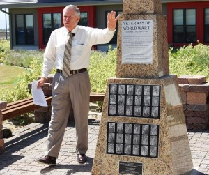 Veterans Home Administrator Norman Andrews helps to unveil the World War II monument.