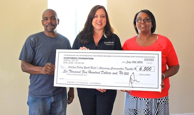 """SunPower Representative Nikki Franko (center) presents a check Thursday, July 31 to AV YouthBuild Construction Manager David Woodman (left) and Board Member Leslie Woodman (right). The funds will be used to provide education, career development services and leadership development opportunities to """"at potential"""" young people in the community. (Photo by JAMAAL BROWN)"""
